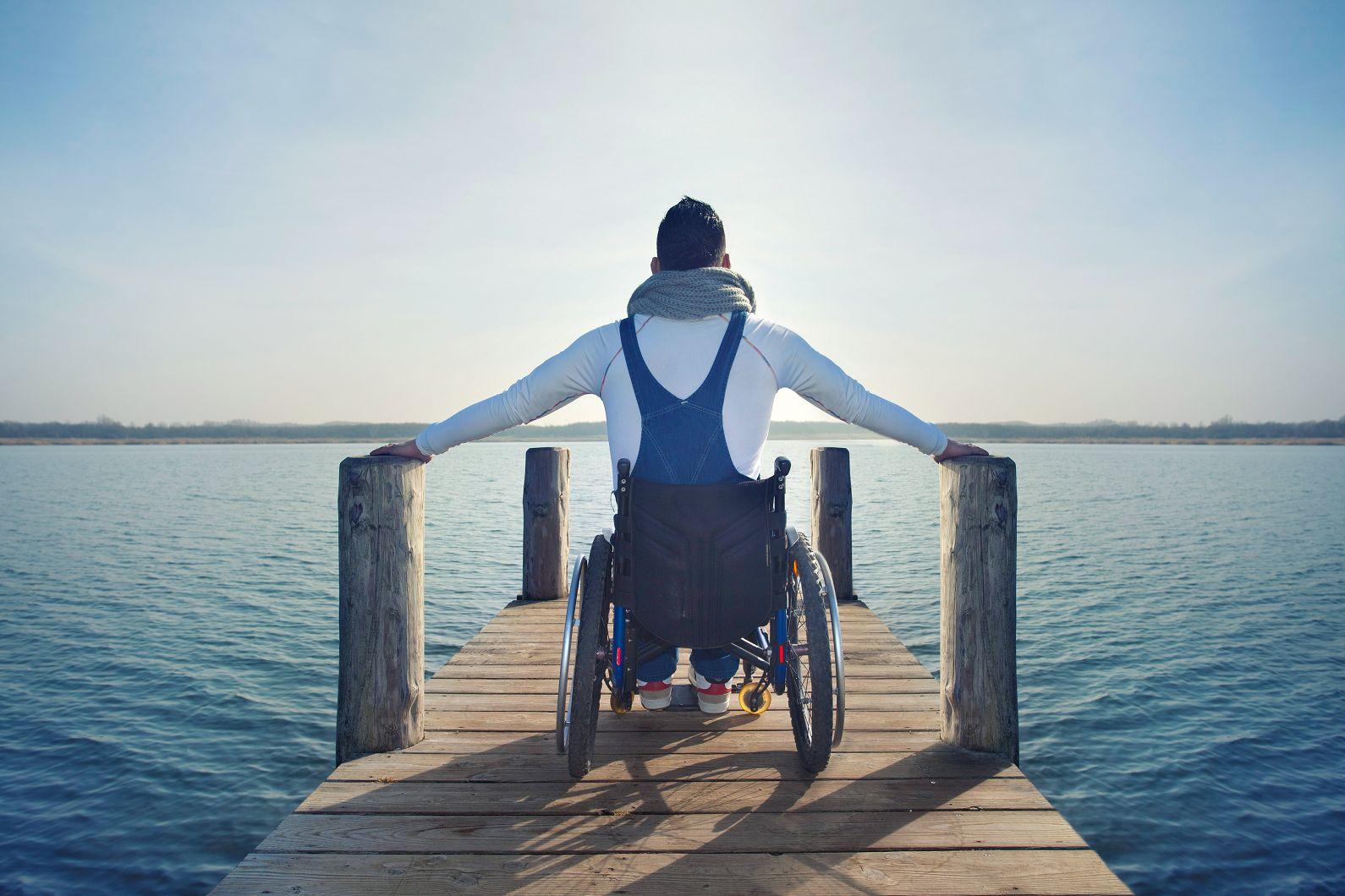 Rollstuhlfahrer auf Steg am Meer
